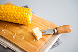 Corn cob on wooden board with pat of butter on corn skewer