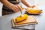A woman's hand putting butter on corn on the cob on board