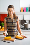 Elegant woman in kitchen smiling while putting butter on corncob