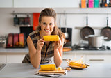 Smiling woman leaning on kitchen counter holding corncob