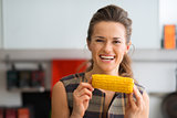 Smiling woman holding corn cob