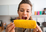 Closeup of woman opening mouth wide to take bite of corncob