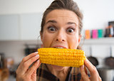 Teasing, happy woman taking big bite of corn on the cob