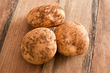 Three Unwashed Potatoes on a Wooden Table