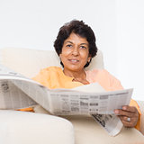 Indian mature woman reading newspaper