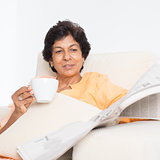 Indian mature mother reading newspaper