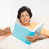 Indian mature woman reading book