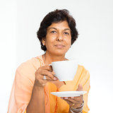 Indian mature woman drinking coffee