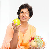Indian mature woman eating fruits