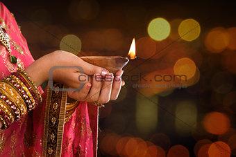 Close up Indian woman hands holding diya light