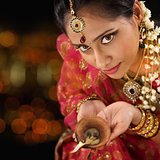 Indian woman hands holding diwali light