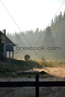 Foggy landscape with cottage in the mountains at the summer morn