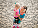 Young mother holding daughter in arms and smiling on the beach