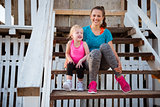 Mother and daughter in fitness gear sitting on beach hut steps