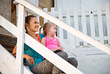 Smiling mother in profile on beach house steps with child