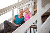 Laughing mother and daughter sitting on beach house steps