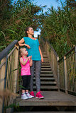 Happy woman and daughter in fitness gear on steps at beach