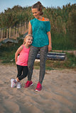 Happy mother and daughter in fitness gear standing on beach