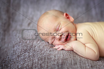 sleeper newborn baby on a gray background