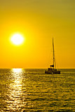 Catamaran sailboat at golden sunset