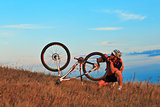 Man cyclist repairing a bike  against blue sky