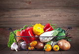 Fresh vegetables in basket on wooden board
