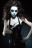 Young woman in the image of evil gothic freak clown with scissors. Grunge texture effect