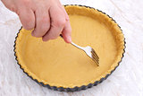 Woman using fork to prick holes in an uncooked pie crust
