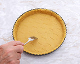 Woman finishes pricking holes in a pastry pie crust