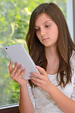 Young girl reading information on a tablet computer