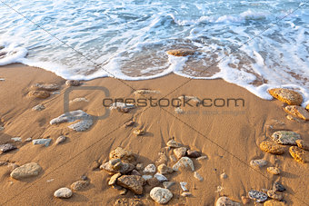 Wave of the ocean on the beach  with sand and stones