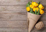 Yellow tulips over wooden table