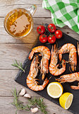 Grilled shrimps on stone plate and beer mug