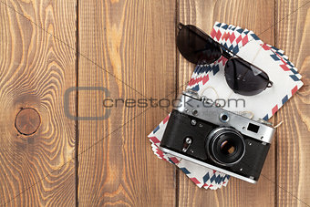 Camera, letters and sunglasses on office desk