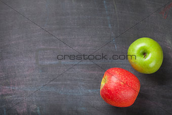 Green and red apples on blackboard or chalkboard background
