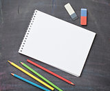 Blank notepad and colorful pencils on blackboard background