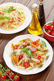 Spaghetti and penne pasta with tomatoes and basil
