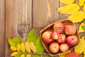 Apples in bowl and colorful autumn leaves on wooden background