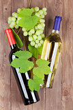 Grapes, red and white wine bottles