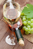 White wine glass, bottle and grapes
