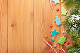 Christmas wooden background with snow fir tree, gingerbread cook