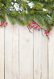 Christmas wooden background with fir tree and holly berry