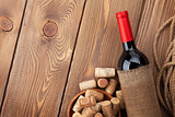 Red wine bottle and corks over wooden table background