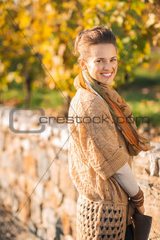 Portrait of smiling elegant brunette woman in autumn park