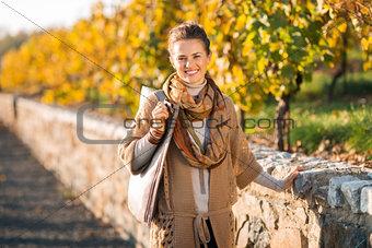 Portrait of happy elegant brunette woman in autumn park