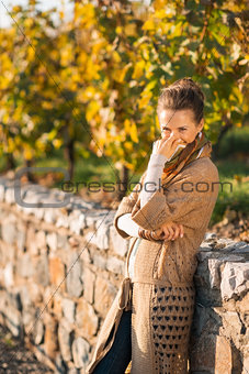 Portrait of cheerful  woman in autumn park hiding behind scarf