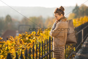 Portrait of smiling and looking down woman in autumn outdoors
