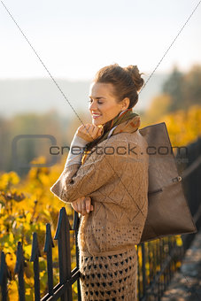 Portrait of happy elegant woman relaxing in autumn park