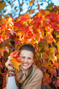 Portrait of happy woman with autumn leafs in front of foliage