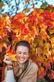 Portrait of smiling woman with autumn leafs in front of foliage